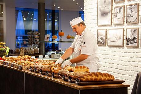 Bäcker mit Brotsortiment in der Bäckerei Richemont