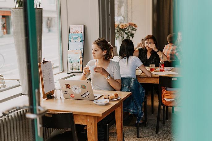 Studentin beim Arbeiten und Kaffee trinken im Restaurant Libelle