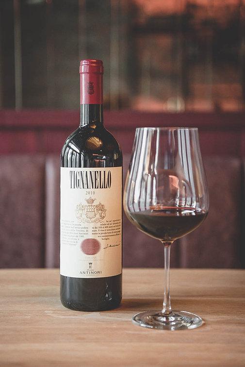 Eine Flasche Tignanello 2010 Rotwein und ein volles Weinglas daneben