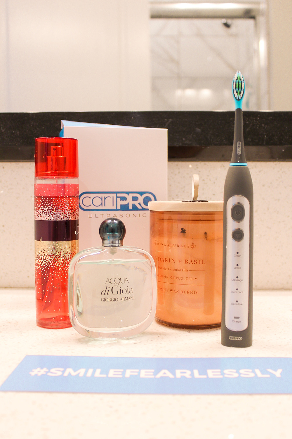 cariPRO electric toothbrush sitting on bathroom counter with perfume and candle
