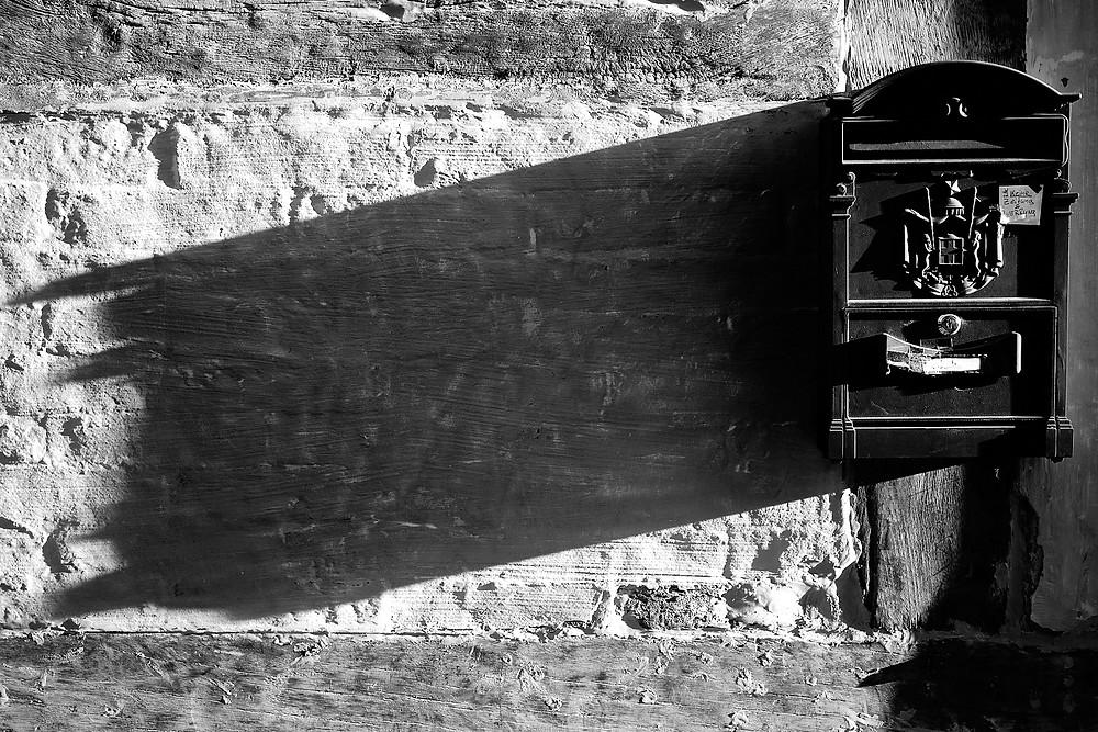 Der lange Schatten eines alten Briefkastens an einer Hauswand in schwarz weiß