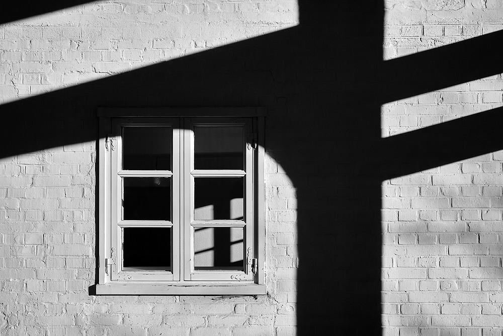 Der klare geradlinige Schatten von Balken auf einer Hauswand