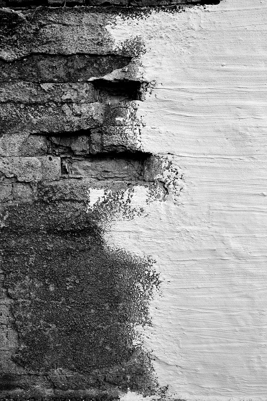 Eine Steinwand die aussieht, als würde das weiße Wasser auf die schwarze Küste treffen