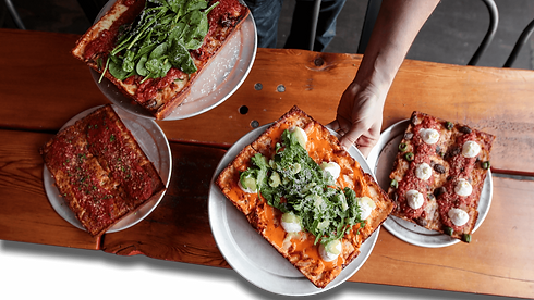 Hand holding Detroit-style pizzas from Iron Born Pizza in Pittsburgh