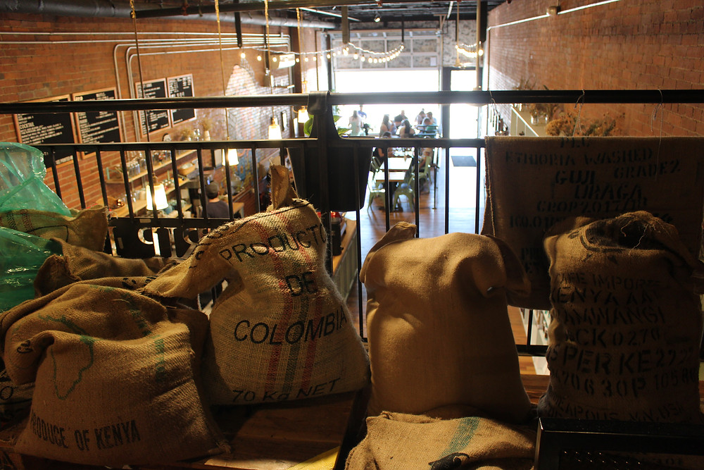 sacks of coffee beans stacked in De Fer Coffee