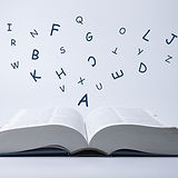 English dictionary with letters flying o