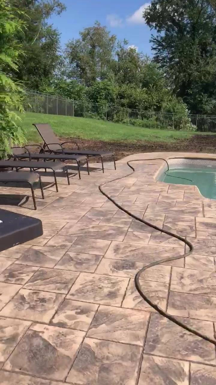 Recently finished ashlar cut slate concrete pool surrounding.