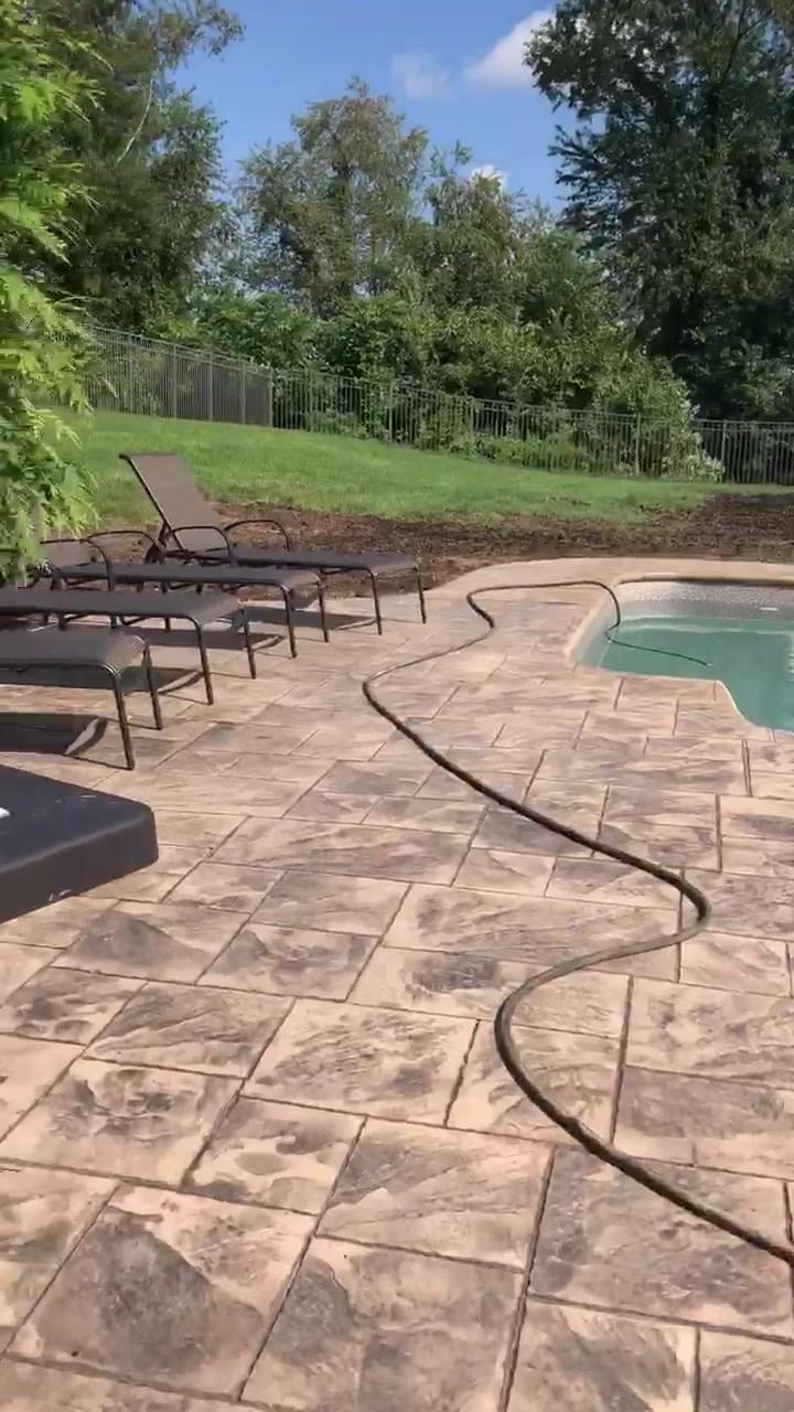 Recently finished ashlar cut slate concrete pool surrounding.