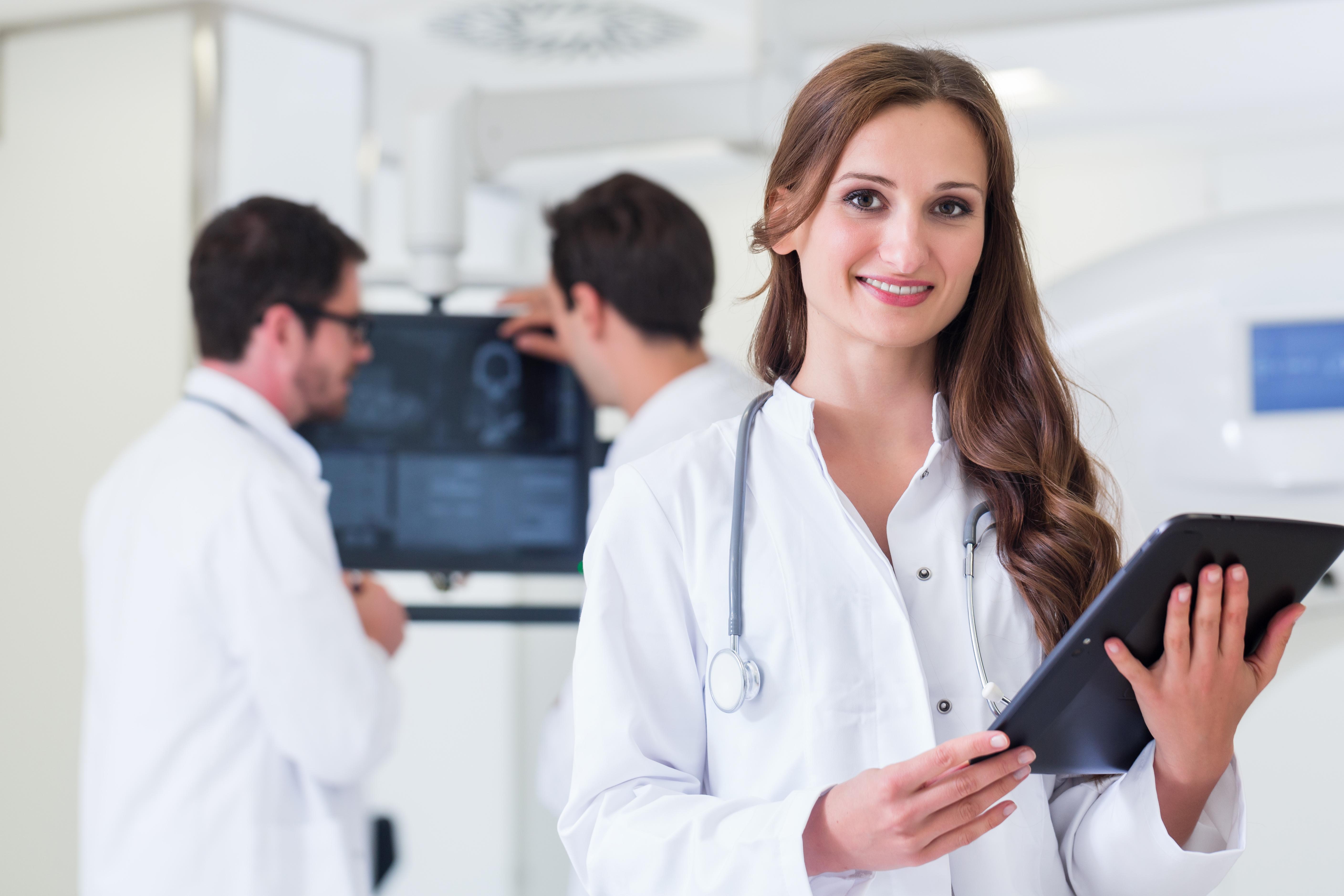 Ärztin_mit_Kollegen_im_Krankenhaus_steht_an_CT_Gerät_mit_Ergebnissen_der_Untersuchung-1