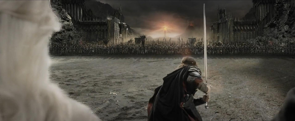 A still from the film The Lord of the Rings: Return of the King. In the final battle scene at the Black Gate of Mordor, the character Aragorn holds his sword high and charges into the battlefield of waiting orcs.