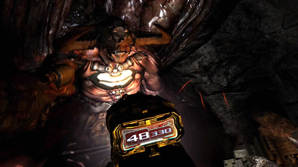 Screenshot from virtual reality game DOOM 3: VR Edition, a Cyberdemon enemy towers over the player, illuminated by a flashlight. The player aims a futuristic gun at the enemy. There is a glowing interface on the gun that displays ammo.