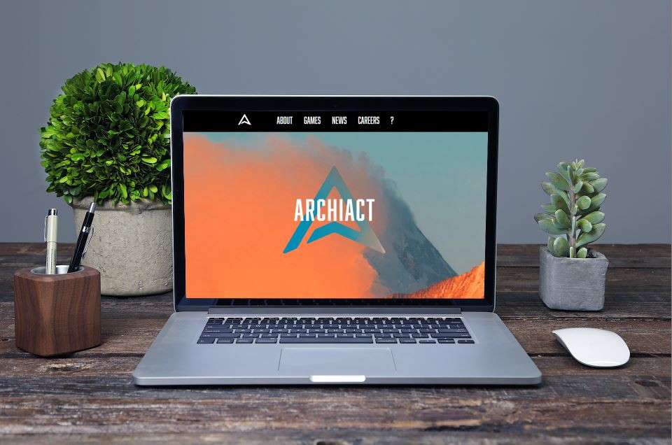 A photograph of a laptop that sits on a desk, with a computer mouse, a pen cup, and plants nearby. On the laptop screen, the orange and blue website for virtual realty game studio Archiact appears, featuring the triangular blue logo and the word ARCHIACT in bold white text.