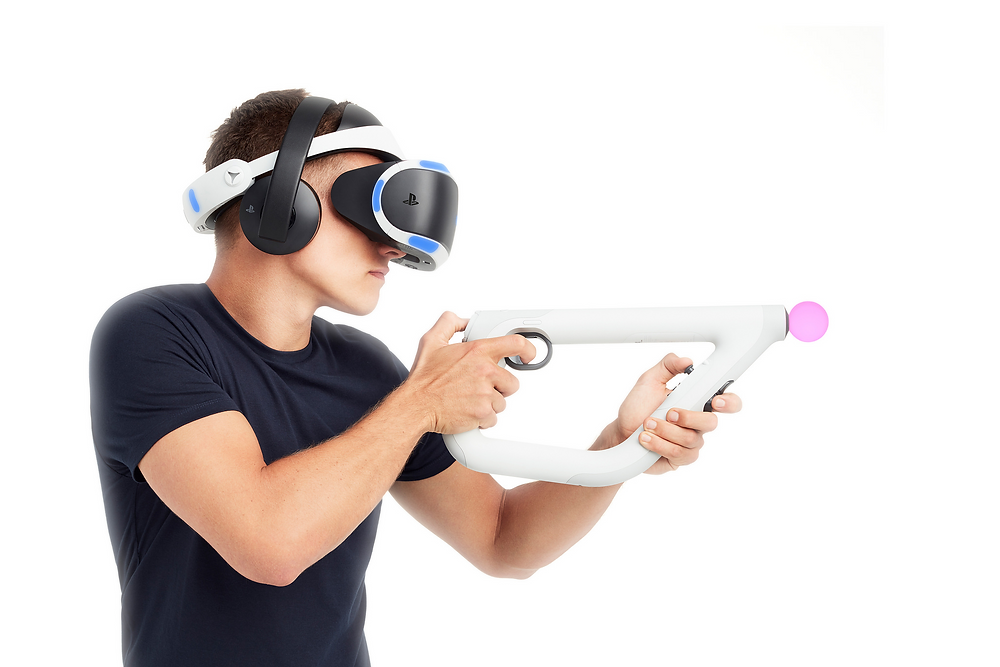 A promotional image for the PlayStation VR Aim Controller, showing a player wearing the PlayStation VR headset, a pair of headphones, and holding the white Aim Controller like a gun at the ready.