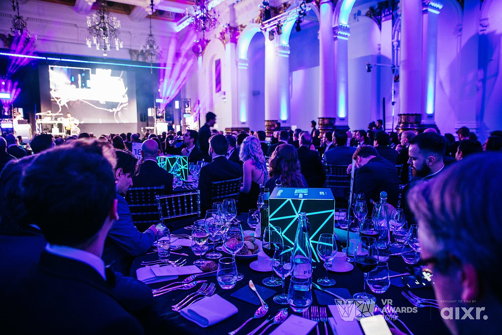 A photograph of the lavish ceremonies honouring the winners of the 2019 VR Awards. Vivid purple lighting illuminates a formal dining hall, where a large crowd of black-tie guests sit at tables before a large stage.