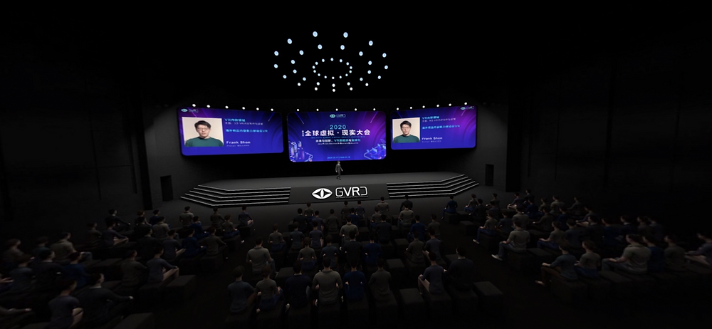 A screenshot of a virtual conference, showing a large crowd of virtual avatars seated in front of a stage. Archiact CEO Frank Shen is on stage as his virtual avatar.