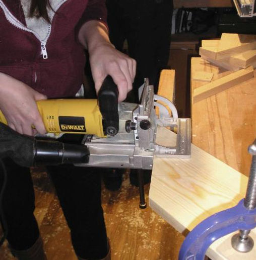 Picture shows a London Woodwork Classes student using a biscuit jointer on the mitre joint of their coffee table top.
