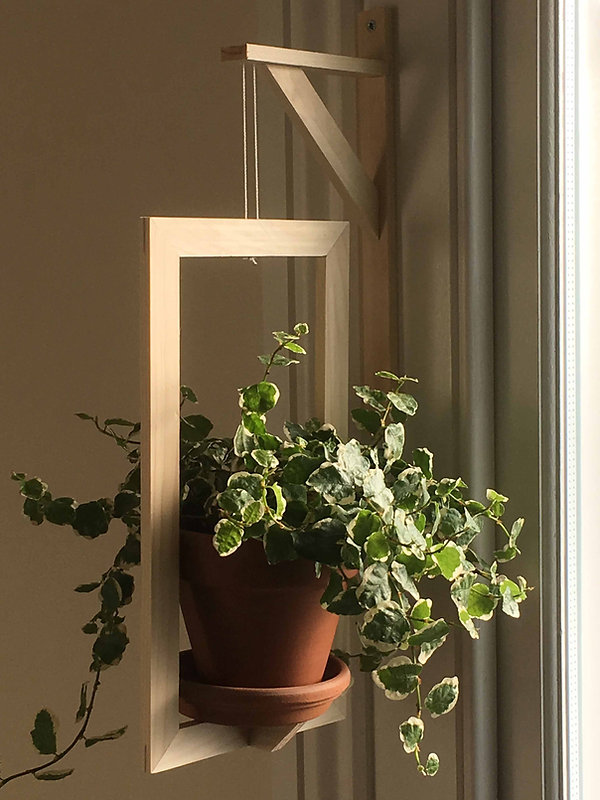 A tempting photograph of the completed plant hanger with a plant in a terracotta pot. The picture shows both the hanger and the frame and the joints uswd in the construction are visible.
