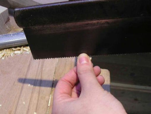 Using the thumb and forefinger to guide the dovetail saw when cutting wast from the tenon.