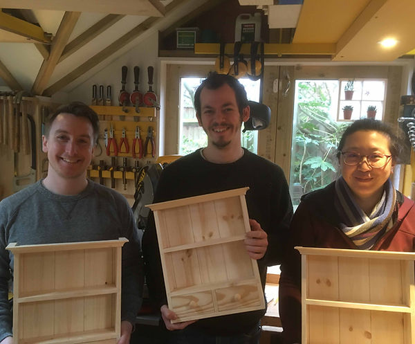 Smiling woodwork students having completed the Spice Rack Course holding their spice racks.