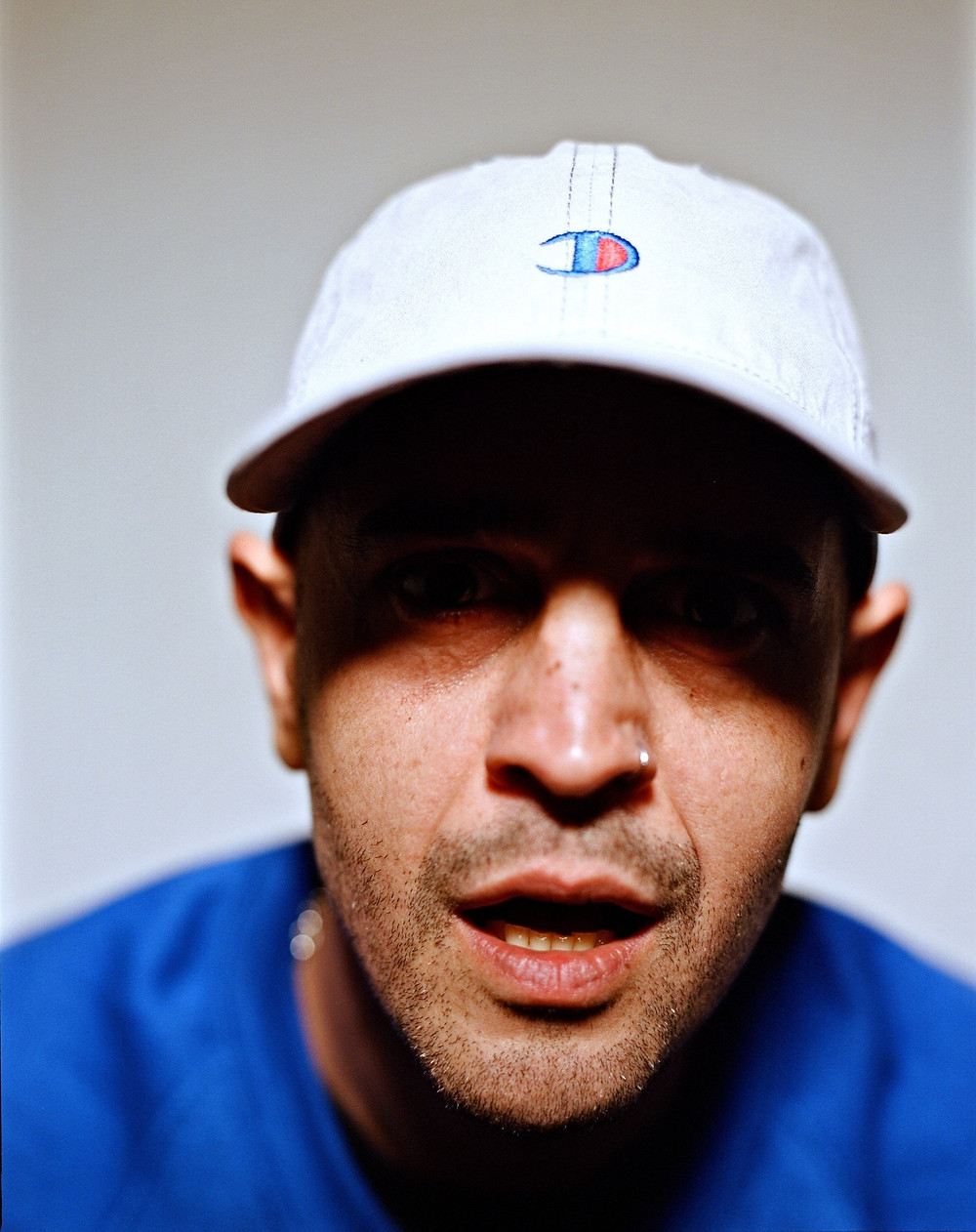 Dabbla in white cap looking into camera in blue sweatshirt.