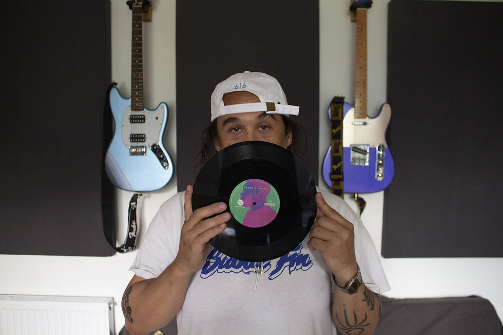 Sumgii holds a vinyl record in front of his face. Electric guitars hang on the wall behind him,