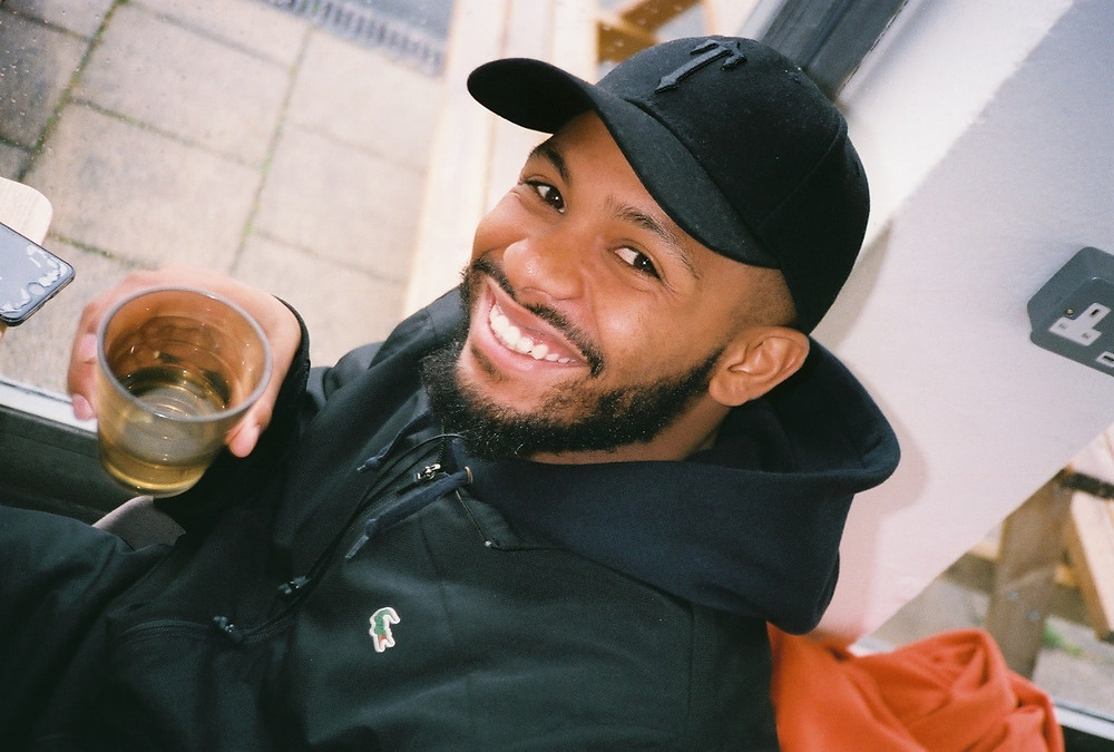 Snowy in black jacket and cap, smiling with a drink in hand.