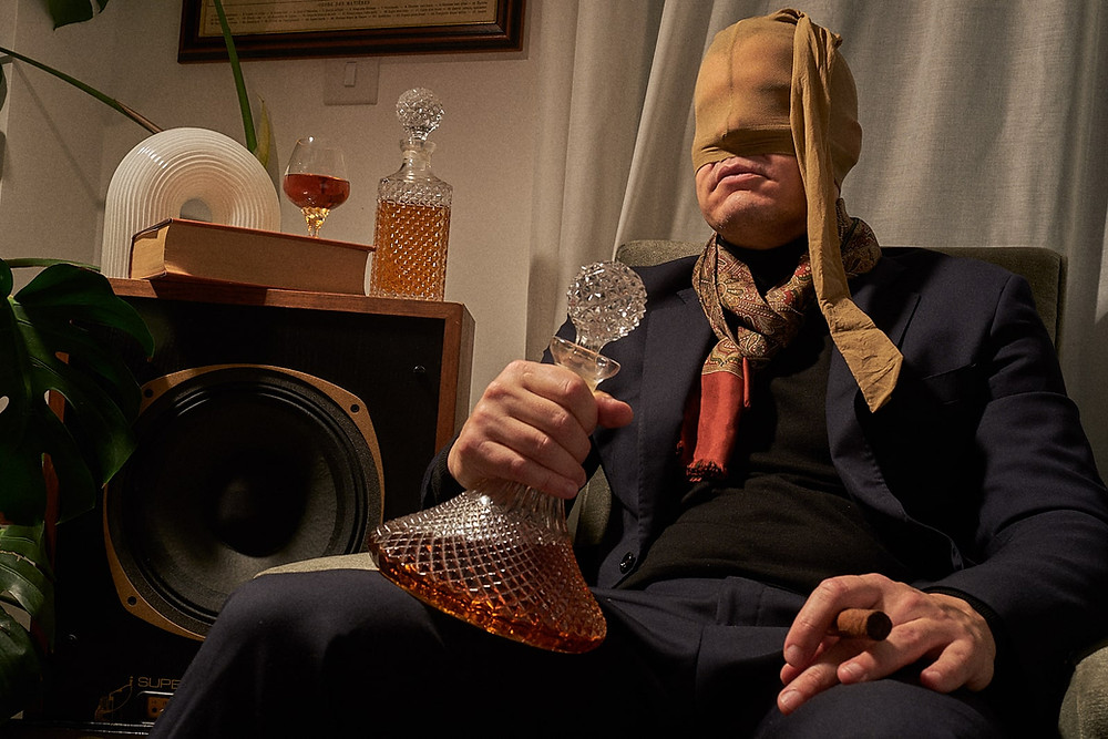 Music producer in a suit and mask. Cigar in hand and glass decanter.