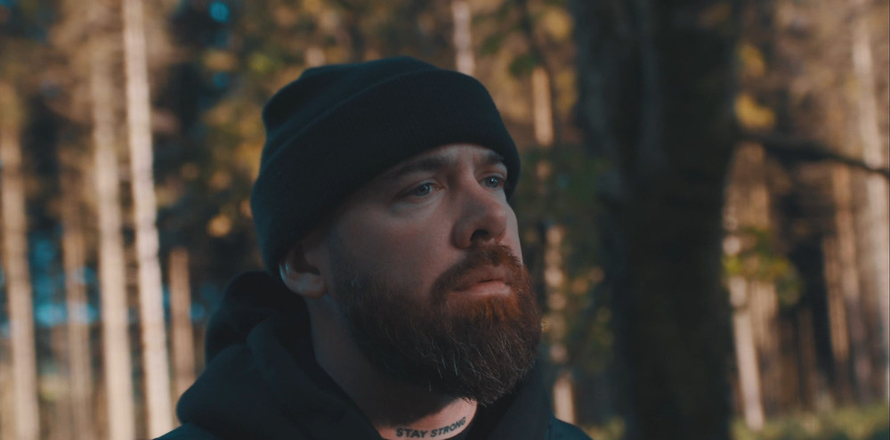 Close-up headshot of Illaman in the woods, looking pensive in a beanie.