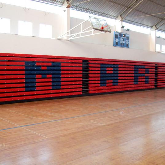 Totalbilde av sammenslåtte vogue benkeseter til teleskoptribune, rød og blå med klubbens initialer