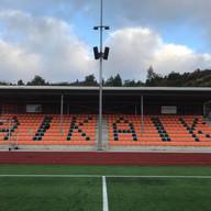 Tribune til Arendal Idrettsklubb i oransje og sort med klubbens initialer