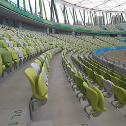 Profilvisning Flerfargede tip-up tribunestoler montert i bakvegg av betongtrapp