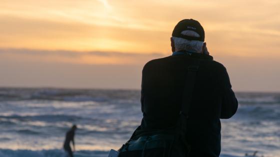 Older man taking photo of sunset