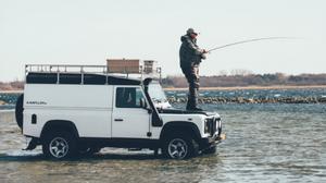 Man fishing from bonnet of car