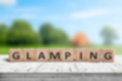 Glamping sign on wooden planks in the su