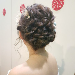 Neat full updo with flowers in hair