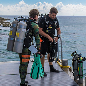 Technical divers in doubles prepare for a dive.