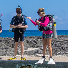 A dive instructor demonstrating equipment setup at Divetech Grand Cayman.