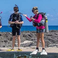 A dive instructor demonstrating equipment setup at Divetech Grand Cayman.