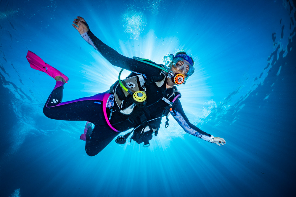 Shot of a diver with sun rays behind her.