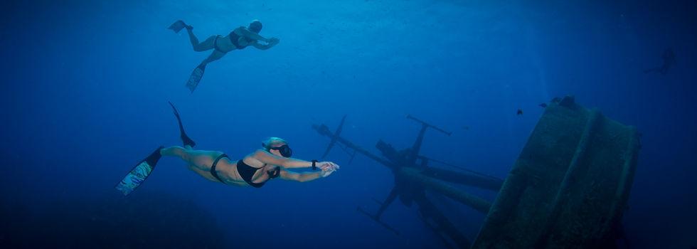 Bikini-clad freedivers on the wreck of the USS Kittiwake
