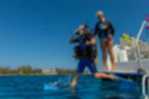 A junior Open Water diver doing a giant stride entry off the dive boat