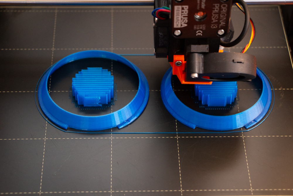 My Prusa I3 mk3 3d printer, making some blue diffusers for my Inon Z330 strobes.