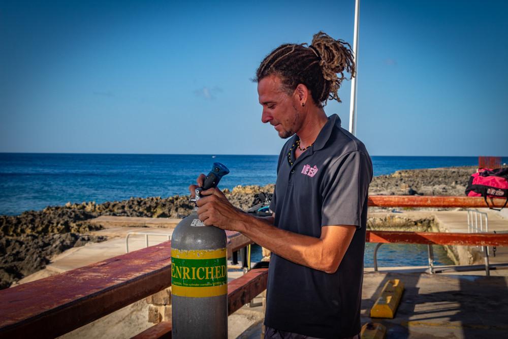 Dive instructor Ragime Powery, analyzing a tank of nitrox.