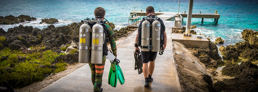 Technical divers on backmount doubles, prepare to dive off one of Grand Cayman's main wall sites