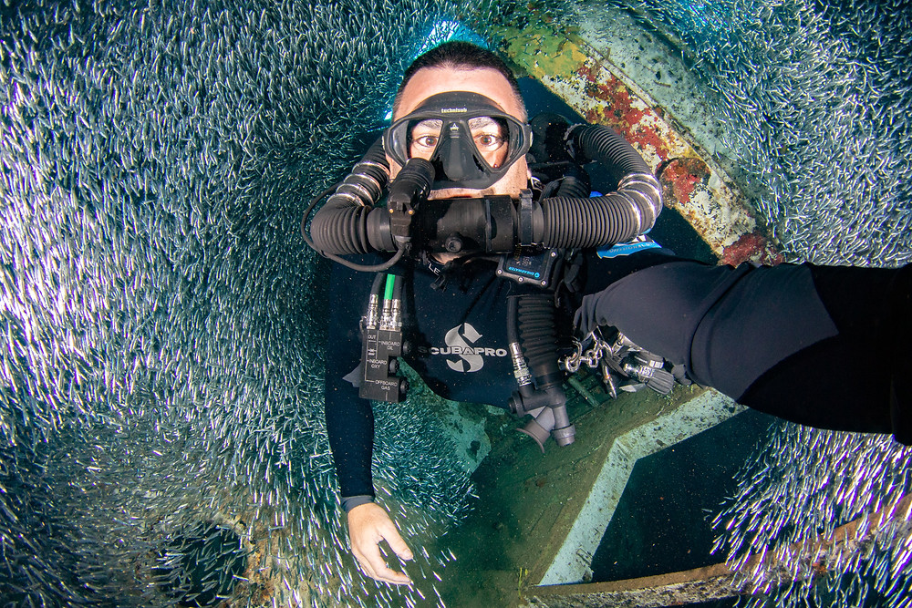 A rebreather diver swimming through a school of dwarf herrings, also known as silversides.