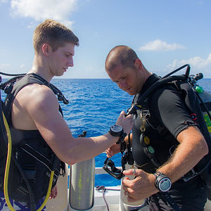 A scuba instructor demonstrates a pre-dive check.