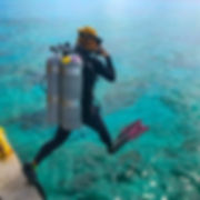 A tech diver, entering the water.