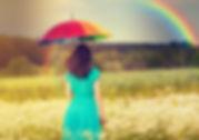 Mujer con paraguas caminando por el campo bajo un arcoiris