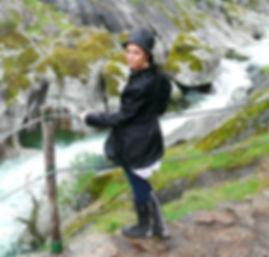 Mujer bajo la lluvia al lado de un río