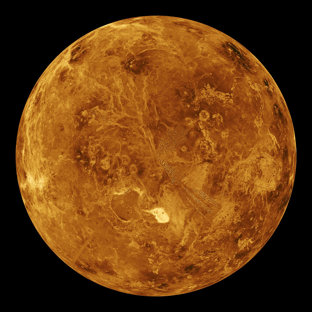 This photo shows a global view of the northern hemisphere of Venus. It's an yellow-rust colored planet.